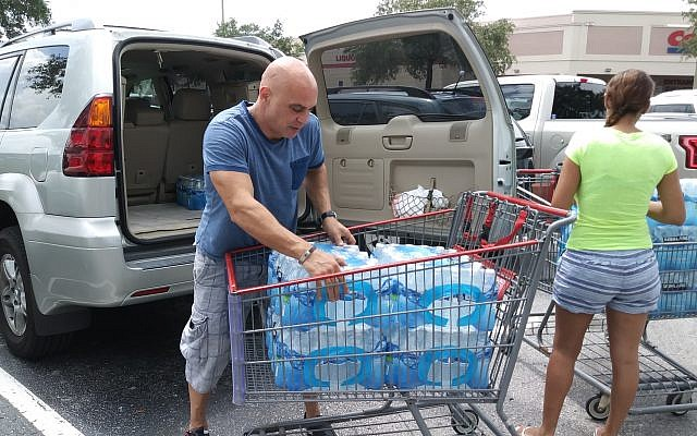 Ali Alchikh and his wife, Najoua Laroui, found replenished supplies of bottled water at Costco and purchased it for their extended family September 5, 2017, in Tampa, Florida. (Jonathan Capriel/The Tampa Bay Times via AP)