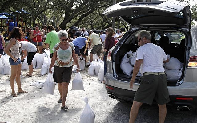 Helen Conklin carries sandbags as her husband, John Conklin, loads the car at Lealman Community Park, 3890 55th Ave. N. in St. Petersburg, September 5, 2017. (Lara Cerri/The Tampa Bay Times via AP)