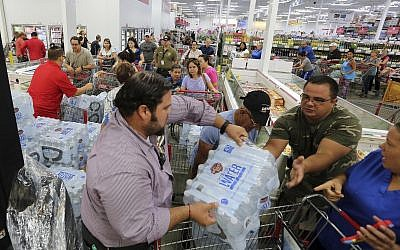 This Sept. 5, 2017 photo shows residents in a long line waiting to purchase water at BJ Wholesale in preparation for Hurricane Irma in Miami. (Roberto Koltun/Miami Herald via AP, File)