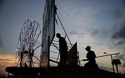 Workers dismantle the facade of a funhouse at an amusement park ahead of Hurricane Irma in Daytona Beach, Fla., Thursday, Sept. 7, 2017. (AP Photo/David Goldman)