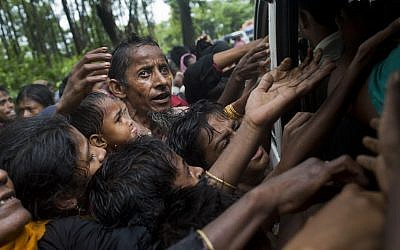 Rohingya scuffle to get aid from local volunteers at Kutupalong, Bangladesh, Friday, Sept. 8, 2017. (AP Photo/Bernat Armangue)