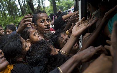 Rohingya scuffle to get aid from local volunteers at Kutupalong, Bangladesh, Friday, Sept. 8, 2017. (AP Photo/Bernat Armangue)