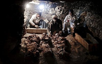 Archaeologists work on mummies found in the New Kingdom tomb that belongs to a royal goldsmith, in a burial shaft, in Luxor, Egypt, Saturday, Sept. 9, 2017. (AP Photo/Nariman El-Mofty)