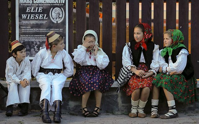Children wearing traditional outfits wait before a march marking one year since the death of Nobel laureate and Holocaust survivor Elie Wiesel in Sighetu Marmatiei, northern Romania, Sunday, September 10, 2017. (AP Photo/Vadim Ghirda)
