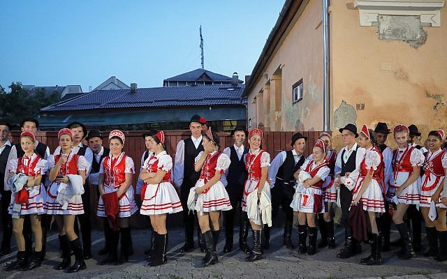 Youngsters wearing traditional costumes wait before a march marking one year since the death of Nobel laureate and Holocaust survivor Elie Wiesel in Sighetu Marmatiei, northern Romania, Sunday, September 10, 2017. (AP Photo/Vadim Ghirda)