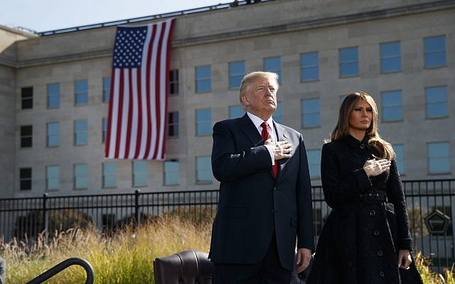 """President Donald Trump and First Lady Melania Trump stand, as """"Taps"""" is played during a ceremony to mark the anniversary of the September 11 terrorist attacks, on that day in 2017, at the Pentagon. (AP Photo/Evan Vucci)"""