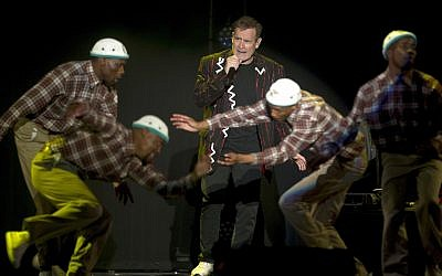 "In this photo taken Saturday, July 2017, South African musician Johnny Clegg, middle, and the dancers perform during ""The Final Journey"" concert at the Grand Arena in Cape Town, South Africa. (AP Photo)"