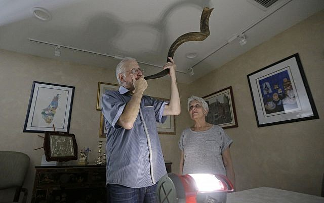 Michael Andron blows the shofar as he prepares for Rosh Hashanah, as his wife Lillian watches as they use a battery powered lantern to illuminate the room at their home, Tuesday, Sept.19, 2017, in Miami. (AP/Alan Diaz)