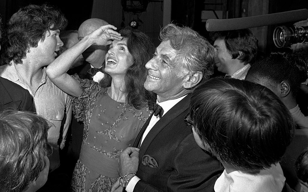 In this Monday, June 5, 1972 file photo Jacqueline Kennedy Onassis, center left, stands with conductor-composer Leonard Bernstein, center right, as she shields light from her eyes while looking up at the stage in the John F. Kennedy Center for the Performing Arts, in Washington. (AP Photo, File)