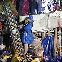 A ladder is raised to search and rescue team members during rescue efforts at the Enrique Rebsamen school in Mexico City, Mexico, Thursday, Sept. 21, 2017. (AP Photo/Anthony Vazquez)