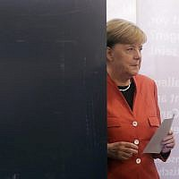 German Chancellor Angela Merkel leaves the election booth as she casts her vote in Berlin, Germany, Sunday, Sept. 24, 2017. (AP Photo/Markus Schreiber)