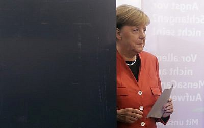 German Chancellor Angela Merkel leaves the election booth as she casts her vote in Berlin, Germany, September 24, 2017. (AP Photo/Markus Schreiber)