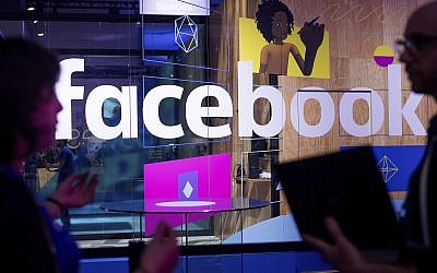 In this Tuesday, April 18, 2017, file photo, conference workers speak in front of a demo booth at Facebook's annual F8 developer conference, in San Jose, California. (AP/Noah Berger)