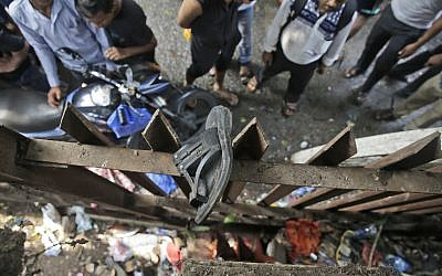 A slipper of an injured commuter is seen stuck on the railing of a pedestrian bridge where a stampede took place at the Elphinstone station, in Mumbai, India, Friday, Sept. 29, 2017. (AP Photo/Rafiq Maqbool)