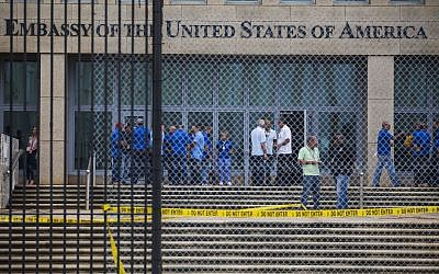 Staff stand within the United States Embassy facility in Havana, Cuba, Friday, Sept. 29, 2017. The United States issued an ominous warning to Americans on Friday to stay away from Cuba and ordered home more than half the U.S. diplomatic corps, acknowledging neither the Cubans nor America's FBI can figure out who or what is responsible for months of mysterious health ailments. (AP Photo/Desmond Boylan)