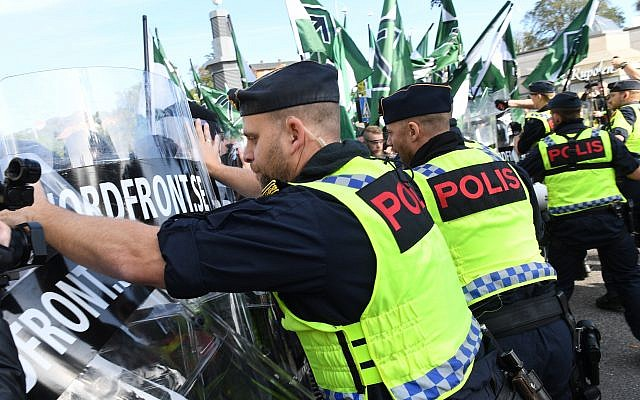 Police officers clash with members of the Nordic Resistance Movement during a demonstration in central Goteborg, Sweden, Saturday Sept. 30, 2017. (Fredrik Sandberg/TT via AP)
