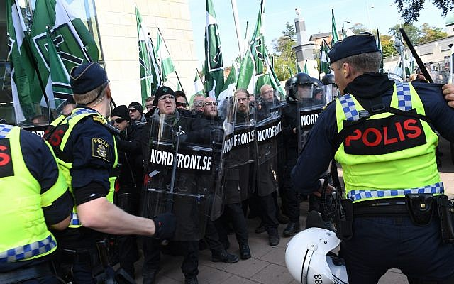Police officers prevent members of the Nordic Resistance Movement walking along a street during a demonstration in central Goteborg, Sweden, Saturday Sept. 30, 2017.(Fredrik Sandberg/TT via AP)