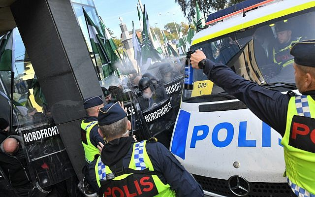 Police officers use a spray toward members of the Nordic Resistance Movement during a demonstration in central Goteborg, Sweden, Saturday Sept. 30, 2017. (Fredrik Sandberg/TT via AP)