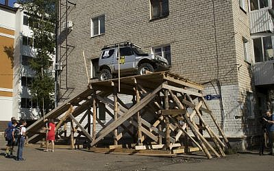A car is parked at a ramp leading up to the window of a Soviet-era apartment in Birobidzhan, Russia, on Wednesday, Sept. 6, 2017. (AP/Iuliia Subbotovska)