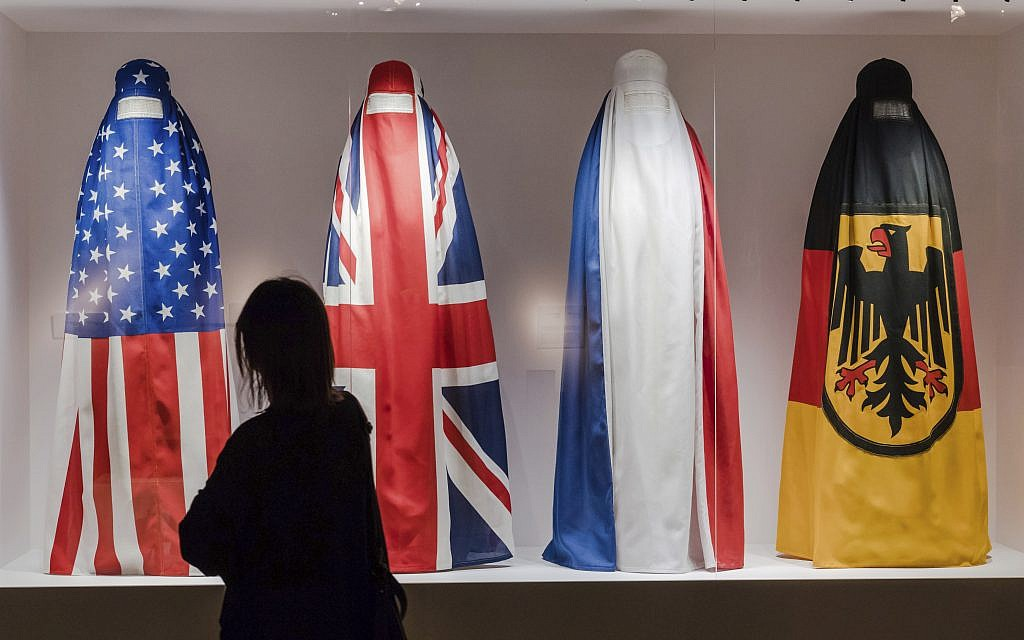 """A Visitor walks by an installation by Haitian artist Jean Ulrick Desert, titled The Burqa Project-On The Borders of My Dreams I Encountered My Double's Ghost for an exhibition """"Islam, It's Also Our History"""" at the Espace Vanderborght in Brussels on Tuesday, Sept. 19, 2017. (Geert Vanden Wijngaert/AP)"""