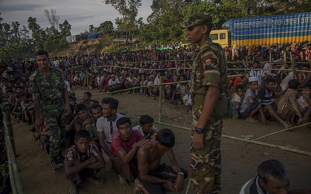 Bangladesh army soldiers stand guard as Rohingya Muslim men, who crossed over from Myanmar into Bangladesh, wait to receive aid during a distribution near Balukhali refugee camp in Bangladesh on September 25, 2017. (Dar Yasin/AP Photo)