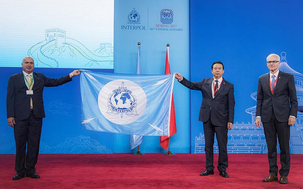 A Palestinian delegate receives the Interpol flag from the president of the International Criminal Police Organization Meng Hongwei, second right, during the Interpol General Assembly, in Beijing, China, September 27, 2017.  (Interpol via AP)