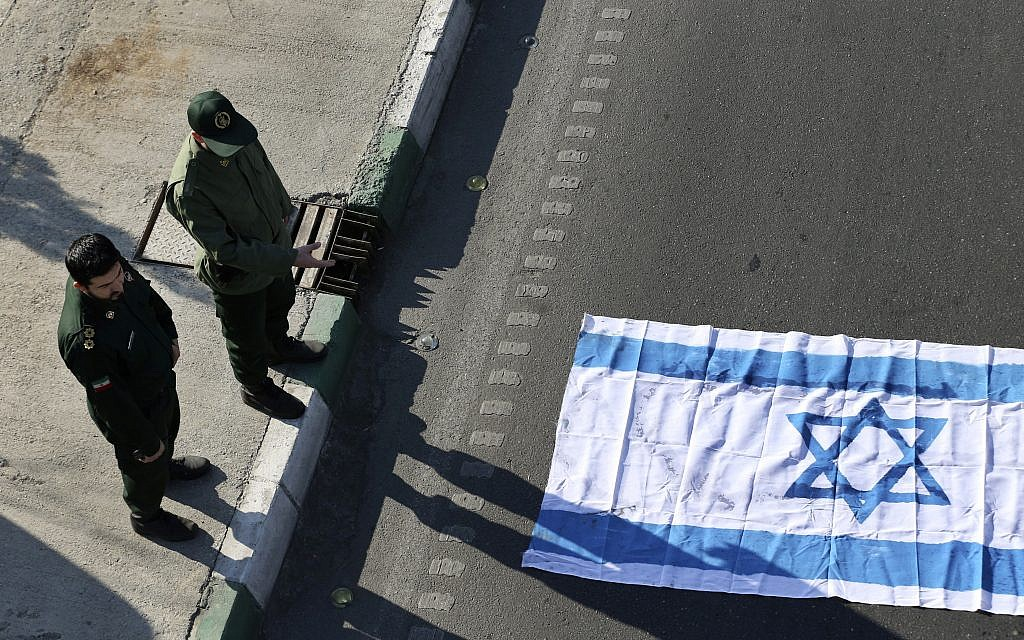 Two members of Iranian Revolutionary Guard stand next to a representation of Israeli flag prepared to set on fire during the funeral ceremony of a Revolutionary Guard Brig. Gen. Mohammad Ali Allahdadi outside the Guard compound in Tehran, Iran, Wednesday, January 21, 2015. (AP/Vahid Salemi)