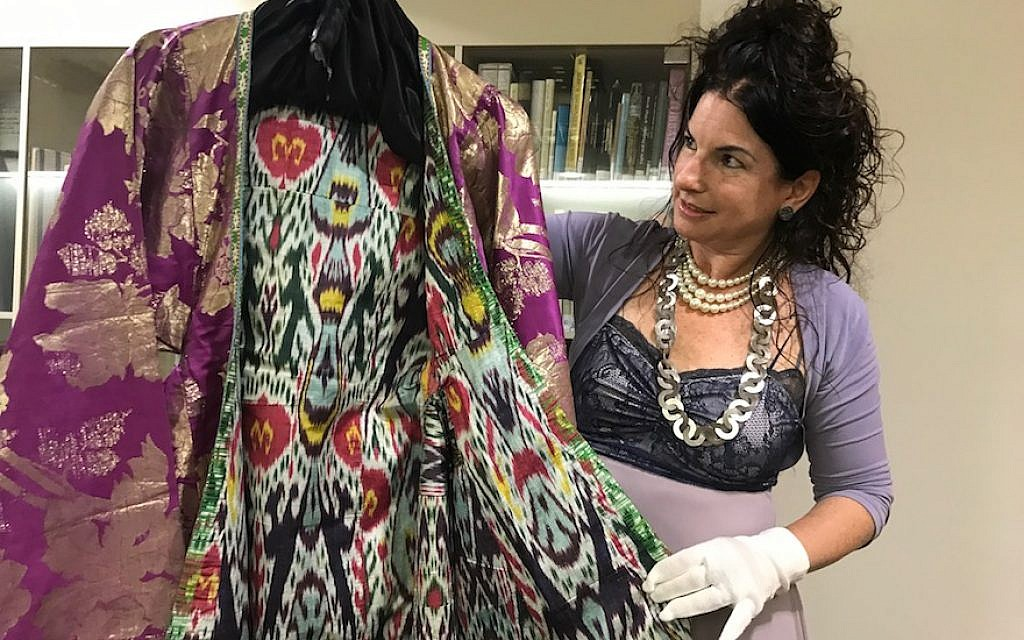 Efrat Assaf-Shapira shows off a Bukharan women's coat from the Jewish clothing collection at the Israel Museum in Jerusalem, September 27, 2017. (Andrew Tobin)