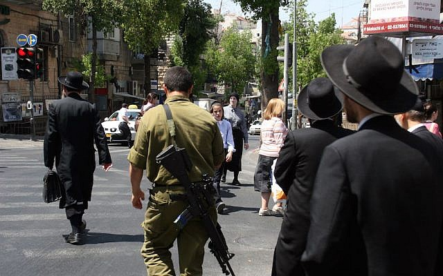 Illustrative: Ultra-Orthodox Jewish men in the Mea Shearim neighborhood in Jerusalem walk along side an Israeli soldier. June 6, 2008. (Lara Savage/ Flash 90)