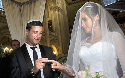 Illustrative: A Jewish couple stand underneath the 'chuppah' during their wedding in a synagogue in Paris, France, July 21, 2013. (Serge Attal/Flash90/via JTA)