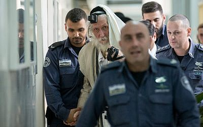 Rabbi Eliezer Berland covers himself with his talit (prayer shawl) at the Magistrate Court in Jerusalem, as he is put on trial for sexual assualt charges, November 17, 2016. (Yonatan Sindel/ Flash90)