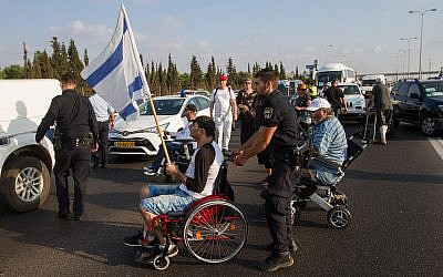 Illustrative photo of disabled protesters blocking a highway outside the town of Yekum on August 14, 2017, as part of demonstrations for higher monthly disability benefits. (Flash90)