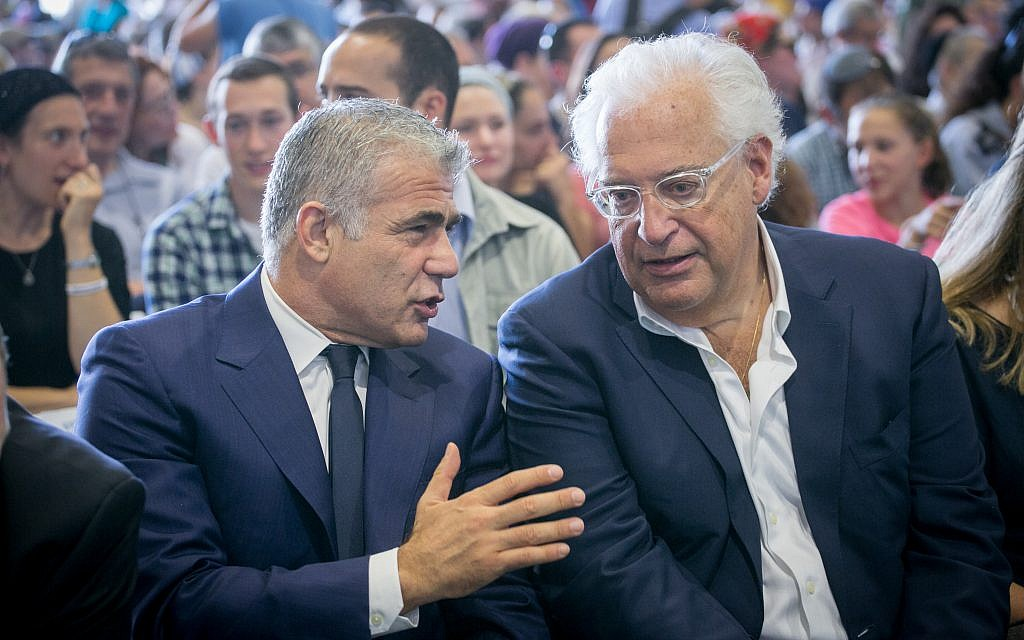 Yesh Atid party leader Yair Lapid talks to US Ambassador to Israel David Friedman, right, at a ceremony for new immigrants from North America at Ben Gurion airport on August 15, 2017 (Miriam Alster/Flash90)