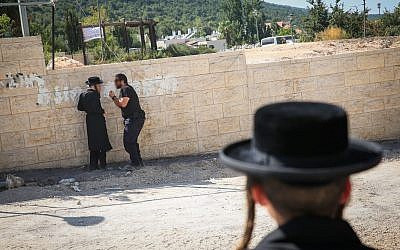 Illustrative: A police officer confronts an ultra-Orthodox protester at a construction site in Meron, northern Israel, on August 16, 2017. (David Cohen/Flash90)
