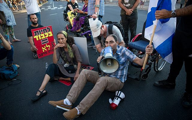 Disabled activists block Ibn Gvirol street in Tel Aviv as part of a protest calling for an increase in government stipends, August 31, 2017. (Miriam Alster/Flash90)