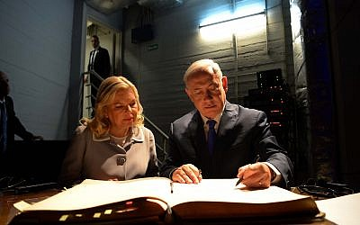 Israeli Prime Minister Benjamin Netanyahu and his wife Sara sign the guest book during a visit at the Israeli embassy in Buenos Aires, Argentina, on September 11, 2017 (Avi Ohayon/GPO)
