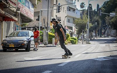 A skateboarder rides down in empty street in Haifa during Yom Kippur on September 30, 2017. (Noam Revkin Fenton/Flash90)