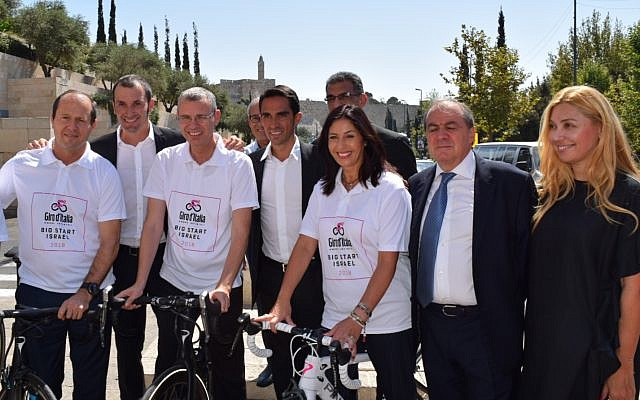 Jerusalem Mayor Nir Barkat (left), Tourism Minister Yariv Levin (on bicycle in middle) and Sports and Culture Minister Miri Regev, with Giro d'Italia organizers and winners celebrating the announcement of the 2018 Giro d'Italia bike race, whose 'Big Start' will take place in Israel in May 2018 (Courtesy 'Big Start')