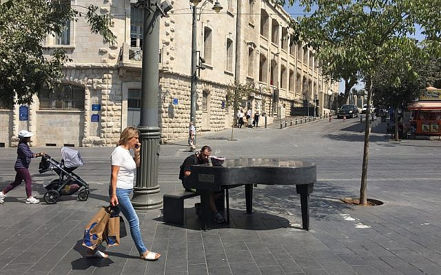 Passersby and a pianist at the Cadenza Piano temporarily installed at a busy crossroads in downtown Jerusalem, bringing music to the public (Jessica Steinberg/Times of Israel)