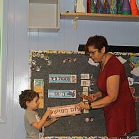 Tamar Pinto, who founded and runs the Gan Gurim preschool, teaching a student the Hebrew days of the week. (Ben Sales/JTA)