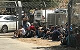 Palestinian laborers sit outside the Har Adar settlement after they were removed from the area by soldiers following a deadly terror attack at the entrance to the community on September 26, 2017. (Jacob Magid/Times of Israel)