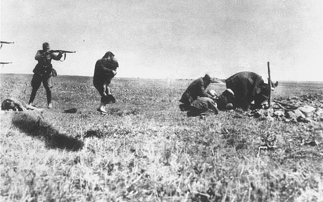 A woman is attempting to protect a child with her own body just before they are executed by Nazi German army mobile killing units (Einsatzgruppen) near Ivangorod, Ukraine in 1942. (Wikimedia commons)