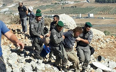 Security forces detain a settler during the demolition of an illegal outpost in the northern West Bank on September 28, 2017. (Courtesy: Honenu)