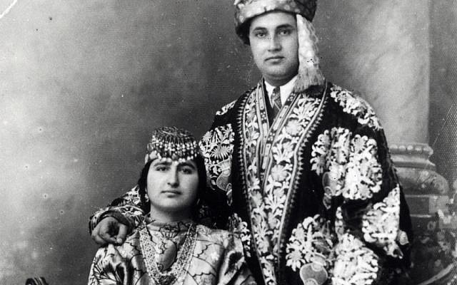 A Bukharan Jewish couple posing in coats lined with ikat weaving. (Courtesy of the Israel Museum/Mauro Magliani)