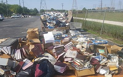 Piles of ruined books from United Orthodox Synagogues of Houston. The congregation lost many of its prayer books and replenished them through donations. (Courtesy of United Orthodox Synagogues via JTA)