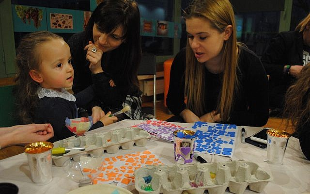 Sara Zielinski, with her mother Elizabeth, center, and a volunteer at a pre-Shabbat program at the Jewish Community Center of Krakow. Sara is part of the inaugural class of Frajda, the first pluralistic Jewish nursery and preschool in Krakow since World War II. (Courtesy of Jewish Community Center of Krakow/via JTA)