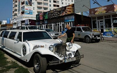 An Israeli visitor to Uman examining a Ukrainian luxury limousine parked on the city's heavily Jewish Pushkin Street, September 8, 2017. (Cnaan Liphshiz/via JTA)