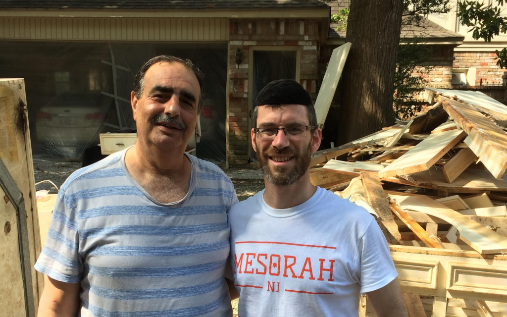 Houston resident Victor Khoury and Rabbi Yehoshua Lewis, director of Mesorah, New Jersey pause during flood recovery efforts. (Courtesy of Lewis)
