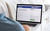 Illustrative image of a man sitting looking at Facebook site on a MacBook. (Prykhodov/Istock by Getty Images)