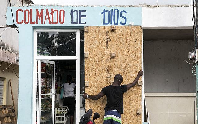 A man covers a bodega's windows before the arrival of Hurricane Irma in Las Terrenas, Dominican Republic, September 6, 2017. (AP Photo/Tatiana Fernandez)